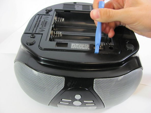 With a plastic opening tool, wedge the bottom shell from the main speaker face along the edge.