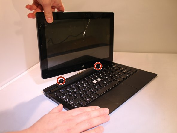 Detach the keyboard from the screen in 2 different places by putting one hand on the keyboard while gently pulling up on the screen with the other hand.