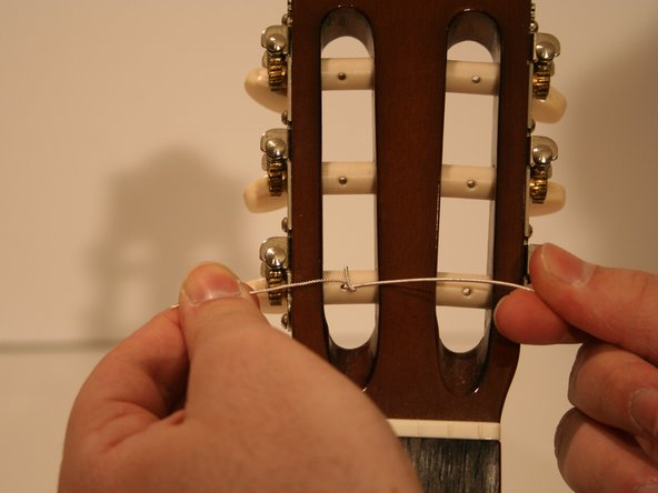Pull the springy end over the tuning peg and to the left side.