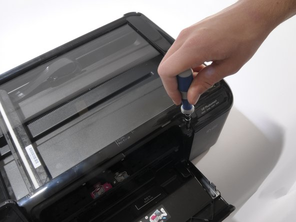 Remove the three screws from the top of the printer with a T-9 screwdriver as shown.