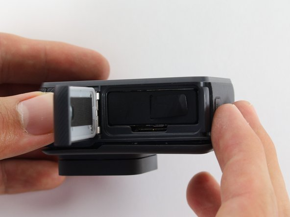 While pressing the button on the bottom of the GoPro, slide the battery door to the side to pop it open.