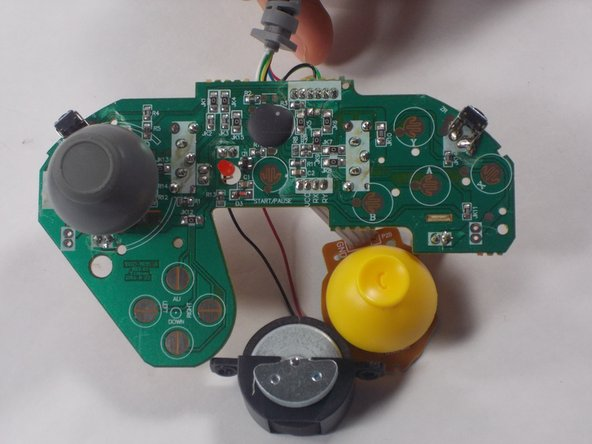 Finally, unscrew the motherboard from the controller and pull the motherboard out. You will see the regular joystick is attached to the motherboard. Firmly, yet gently, pull the joystick out and clean around the are before reattaching.