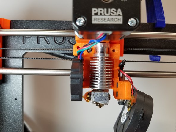 Remove the Extruder Plate carefully, and avoid touching the hot metal print head.
