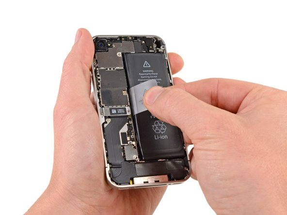 Image 1/2: Use the exposed clear plastic pull tab to peel the battery off the adhesive securing it to the iPhone.