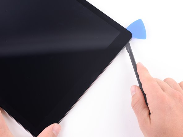 Image 2/3: Slide the blade along the top edge of the iPad, stopping before reaching the front-facing camera.