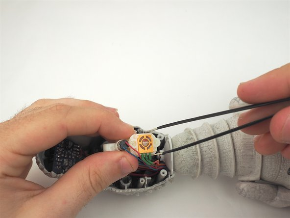 Image 3/3: Use tweezers to gently remove the motor from the rest of the assembly.