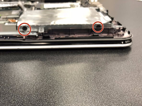 Lift up the hard drive and remove the two Phillips #0 screws that hold the hard drive to the case.