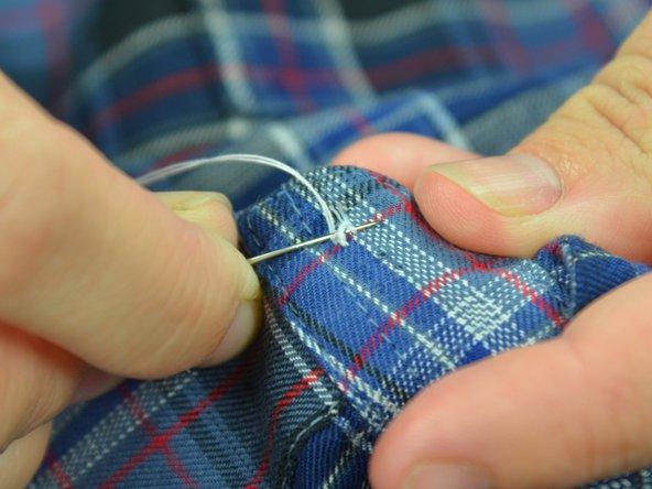Image 2/3: Push the needle through the loops of thread on the underside of the fabric. Be careful not to catch the fabric.