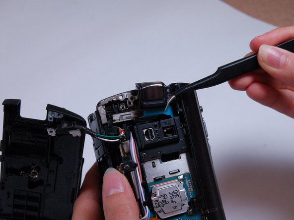 Use the curved tweezers to carefully detach the blue ribbon cable connector from the body of the camera.