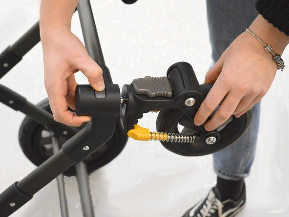 Press the button above the swivel wheel, and pull out the swivel wheel