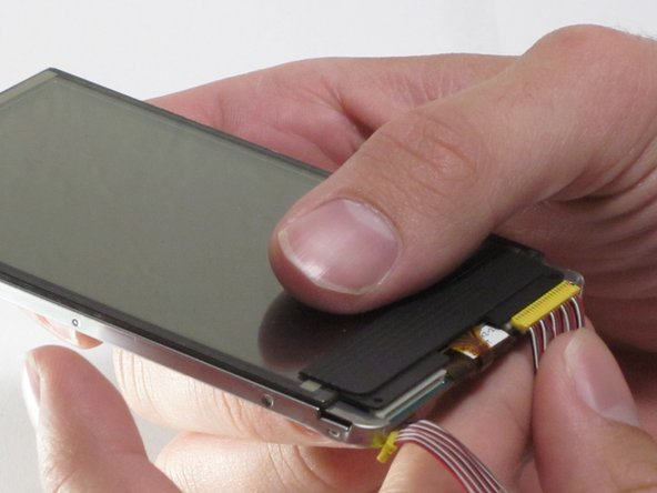 Disconnect the screen from the device by gently pulling the two display data cables away from the bottom of the screen module with your fingers.