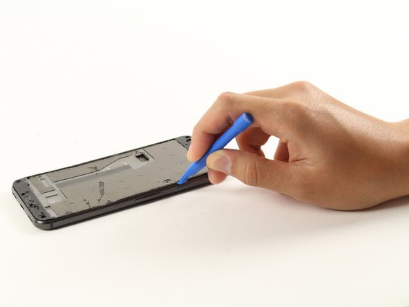 Slide the opening tool across the seam of the device and lift the mid-frame.