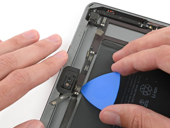 Image 1/3: Carefully insert an opening pick under the logic board, between the front-facing camera and the battery.
