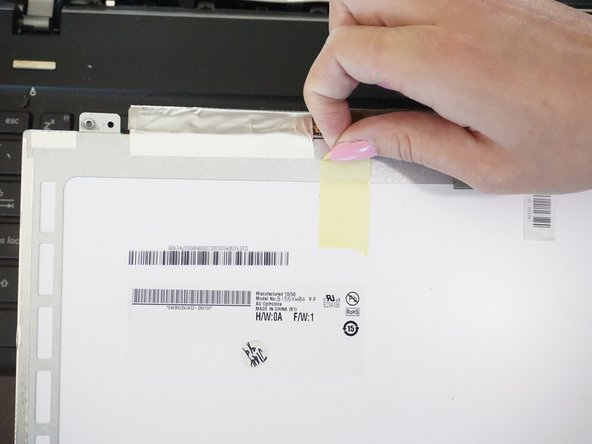 Image 1/2: Peel the yellow tape and then the metallic tape holding the screen's connection to the computer.