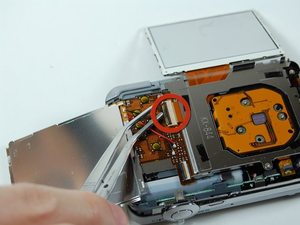 Image 1/3: Pull out the LCD screen with the ribbon from the camera.