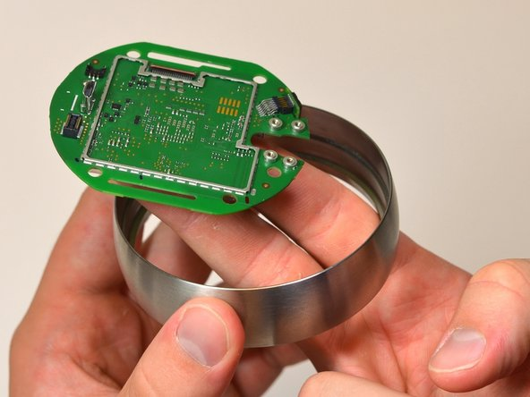 Using one hand to hold the steel ring, carefully lift the motherboard out of the ring using the other hand.