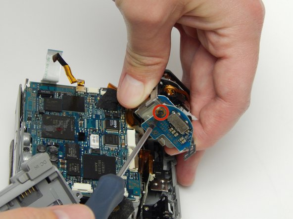 Image 1/3: While gently holding the lens piece, remove the 5 MM Phillips #1 screw.