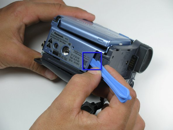 Place a plastic opening tool under the bottom of the blue panel beneath the camcorder.  Using two tools may be useful, if difficult.