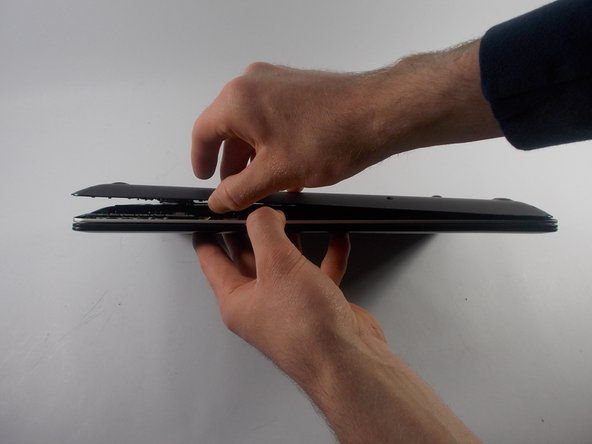 Carefully peel the panel off of the bottom of the laptop.