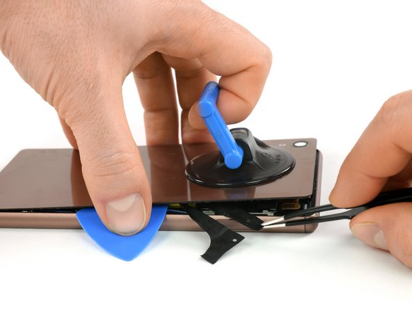 Use a tweezer to pull out two black straps that are attached to two pieces of adhesive right on the battery.