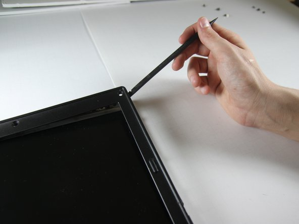 Carefully use a spudger to work around the edge of the screen to lift off the plastic cover