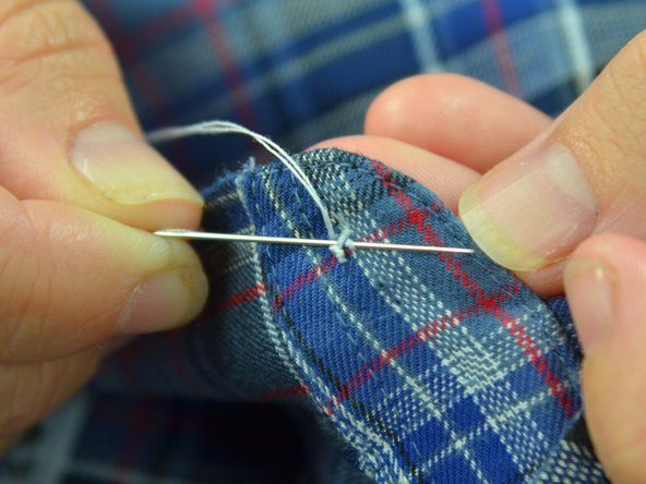 Image 3/3: Push the needle through the loops of thread on the underside of the fabric. Be careful not to catch the fabric.