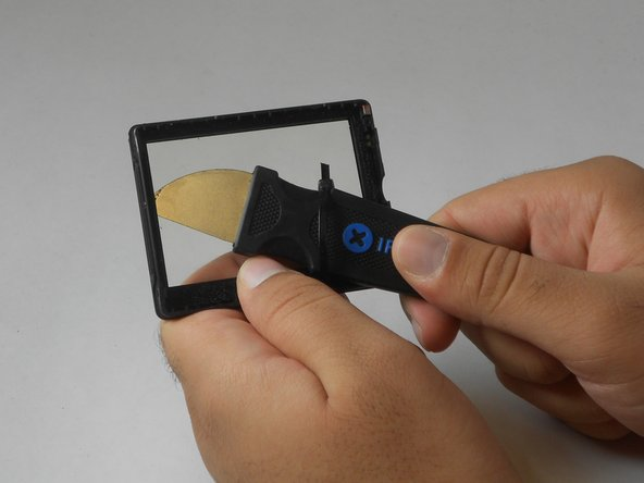 Carefully slide the Jimmy through all corners of the plastic frame until it is detached from the plastic cover.