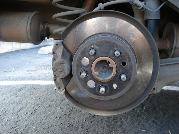 Remove tires by pulling directly away from car exposing rear brake disks and calipers.