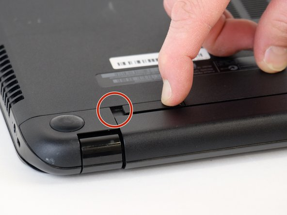 Place your finger on the left latch and slide it towards the center of the laptop.