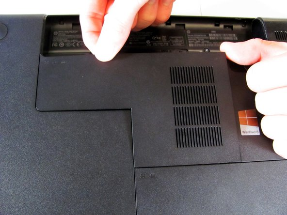 Once the screw is sufficiently loosened, slowly unclip the RAM compartment cover from its slots in the plastic chassis.
