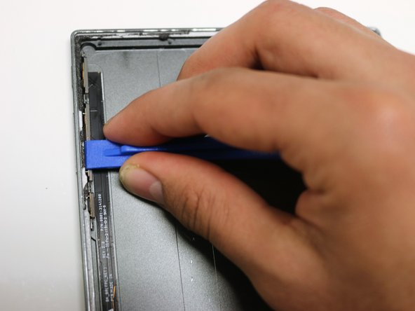 Using a plastic opening tool, pry open the left side of the tablet.