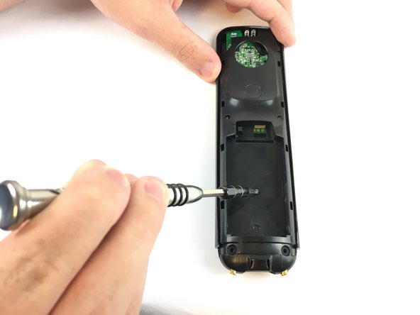 Push the opening tool into the gap along the side of the remote, then slide it across until you hear clicking sounds.