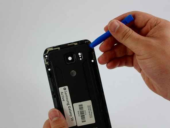 Insert a plastic tool between the frame of the phone and the back cover at the top right corner.