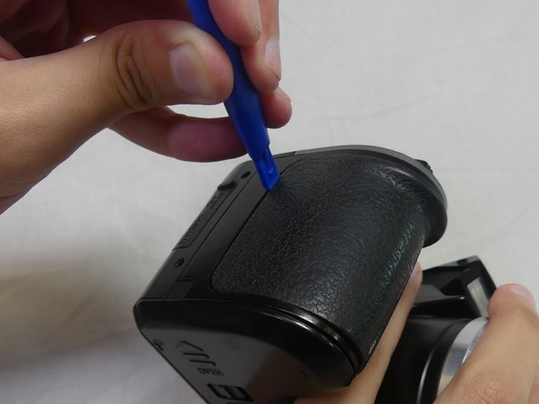 Slide the plastic opening tool along the perimeter of the rubber grip to unbind the glue.