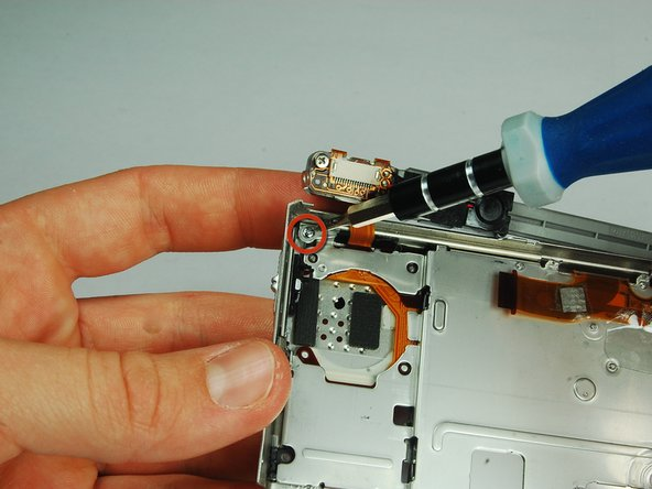 Use a PH00 screwdriver to remove the 2.9 mm phillips screw on the upper left side of the case.