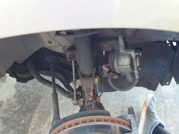 Wiggle the caliper out and off of the pads/rotor, and place out of the way - do not let it dangle by the brake hose.