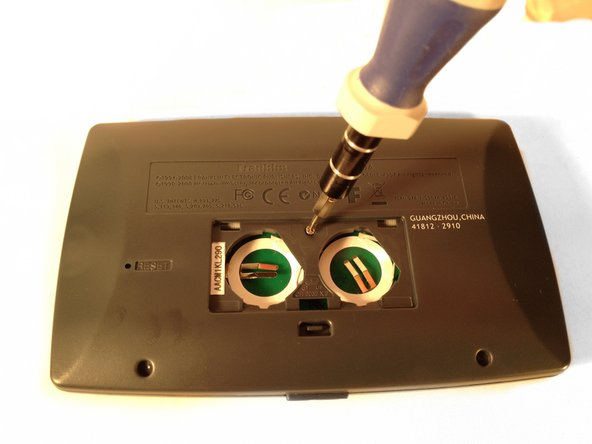 Locate the one screw inside the battery compartment, loosen it, and remove it.