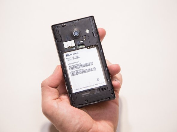 Image 3/3: Lift the battery out of the phone with your fingers by pressing forward and lifting upward.