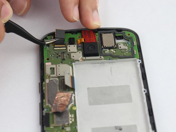 Lift metal clamp at the base of front camera with a plastic opening tool.