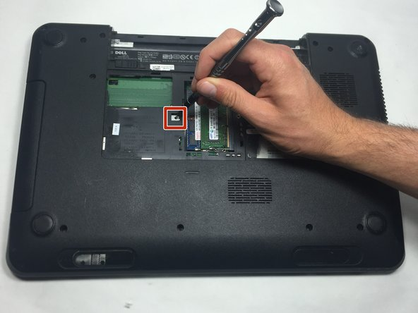 Insert a small screwdriver into the hole and slide the optical drive away from the center of the device. This will slide the optical assembly out from the side of the device.