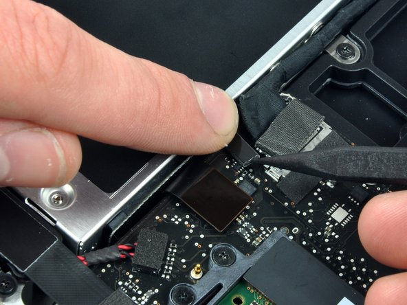 Apple sticks a small strip of clear plastic with adhesive applied to one side to the logic board behind the camera cable connector to keep it in its socket. When moving it out of the way, be sure not to break any surface-mount components off the logic board.