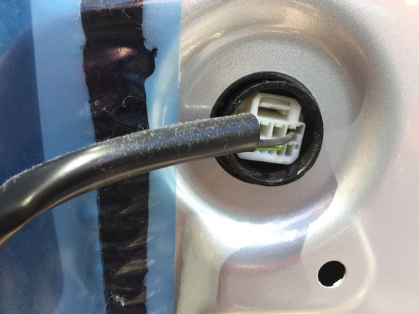 Remove the door lock actuator wiring harness by pressing the harness tab and simultaneously pulling it back and out of the connector housing.