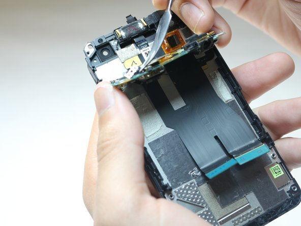 Using tweezers, lift the secondary motherboard from the base of the phone.