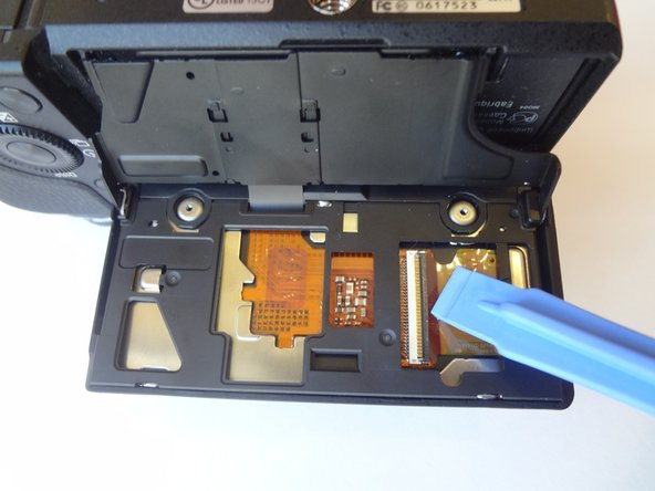 Release the ribbon cable by lifting the black locking latch with the plastic opening tool.