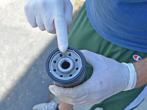 Dip a clean, gloved finger into a new bottle of oil and spread a thin layer of oil onto the gasket of the new oil filter.