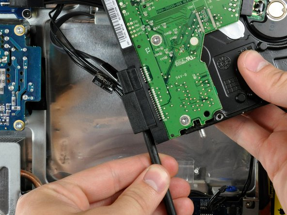 Image 1/2: Twist the spudger to separate the SATA power connector from the hard drive.