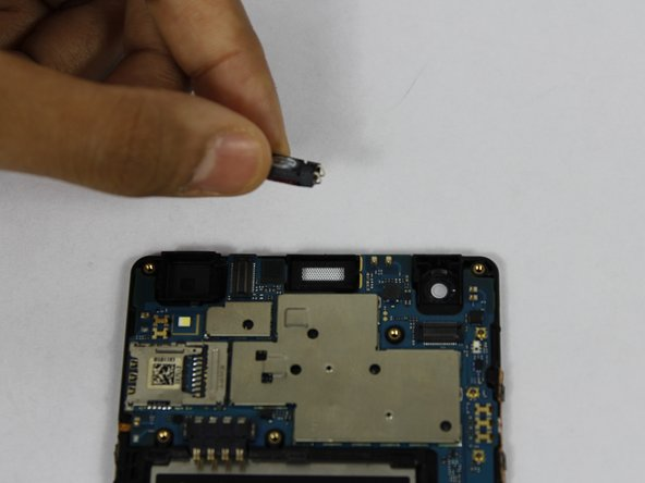 Using a plastic opening tool, pry up the front facing speaker and remove from the phone.