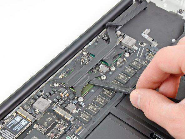 Wenn der Kühlkörper noch am Logic Board zu hängen scheint, obwohl alle acht Schrauben entfernt wurden, dann kannst du ihn mit einem Spudger vorsichtig von den Kontaktflächen zur CPU und GPU ablösen.