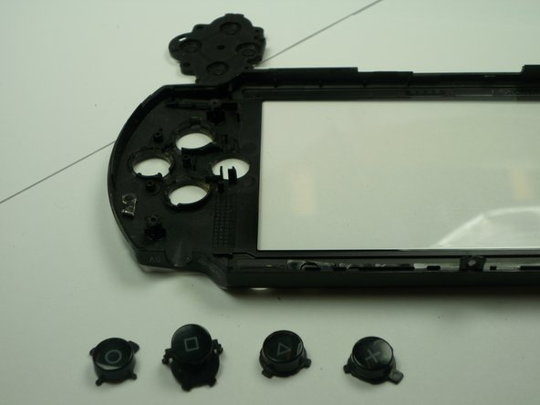 Carefully remove the back rubber to expose the rear side of the buttons as shown. (This can be done using your hands.)