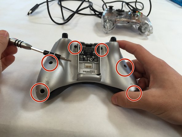 Using a TP Torx T8 Screwdriver, remove all 6 screws from the back of your controller.